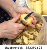 chef peeling potatoes | Shutterstock . vector #553391623