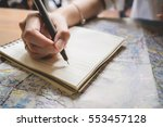 young woman writing in the note ... | Shutterstock . vector #553457128