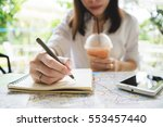 young woman writing in the note ... | Shutterstock . vector #553457440