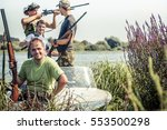 Small photo of Hunters with guns in boat on river bank during hunting season among reed