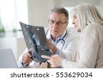 doctor with patient looking at... | Shutterstock . vector #553629034