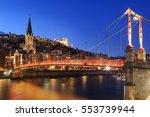 Illuminated Saint Georges footbridge and Vieux Lyon in Lyon, France, at dusk.