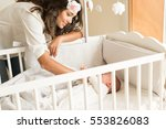 mother putting baby to sleep at ... | Shutterstock . vector #553826083