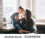 mother kissing her little son | Shutterstock . vector #553898098