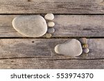 Small photo of Two traces of feet made of pebbles over wooden planks