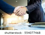 two businessmen shaking hands... | Shutterstock . vector #554077468
