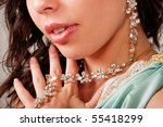 Beautiful young lady shows necklace and earring - stock photo