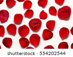 Stock photo  two golden wedding rings is in red rose petals on a white wooden table 554202544
