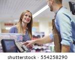 woman next to cash register... | Shutterstock . vector #554258290