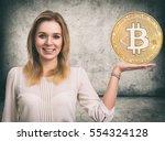 beautiful woman showing golden...   Shutterstock . vector #554324128
