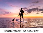 person stand up paddle boarding ... | Shutterstock . vector #554350129