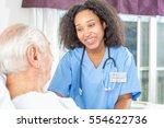 african nurse smiling to elder... | Shutterstock . vector #554622736
