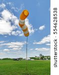 Small photo of Airport windsock on blue sky background in windy weather indicate the local wind direction. Also called: air sock, drogue, wind sleeve, wind cone