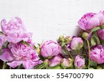 pink peonies on white wooden... | Shutterstock . vector #554700790