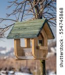 Small photo of Wooden bird feeder with seed mix affixed to the tree