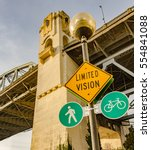 Small photo of Bike lane, walk lane and limited vision signs with Burrard Bridge abutment on background, Vancouver, British Columbia, Canada