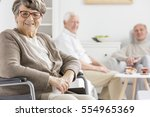 smiled woman on a wheelchair at ... | Shutterstock . vector #554965369