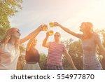 friends enjoying outdoors with... | Shutterstock . vector #554977870