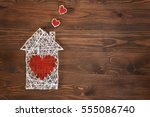 Small photo of Home sweet home. Handmade home symbol with heart shape on wooden background with copy space