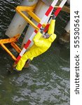 Small photo of specialist in protective suit and mask climbing on ladder above water