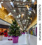 Small photo of View on christmas fir with ornamentation in flower pot in mall with gallery of commercial numbers with sale and pendant ornaments under ceiling before christmas and new year
