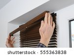 installing wooden blinds. a man ... | Shutterstock . vector #555363838