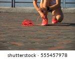 young woman runner tying... | Shutterstock . vector #555457978