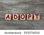 Small photo of Cubes with word ADOPT on wooden background