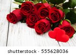Stock photo red roses with hearts on a old wooden table 555628036