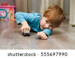 little boy plays with toy car... | Shutterstock . vector #555697990