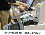 Small photo of Man using pos terminal at the shop (paying credit card for purchases)