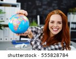Small photo of Cheerful young adult female in red hair holding globe in classroom. Obscured chalkboard behind her.