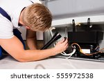 young male technician checking... | Shutterstock . vector #555972538
