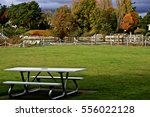 a park bench remains unoccupied ... | Shutterstock . vector #556022128