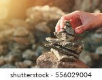 Tourist Hand Making Stone Towe...