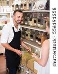 man seller wearing apron... | Shutterstock . vector #556191358