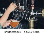 woman pouring cold beer into... | Shutterstock . vector #556194286