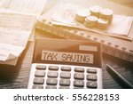 calculator with text tax saving.... | Shutterstock . vector #556228153