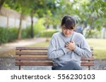 woman has chest pain at park | Shutterstock . vector #556230103