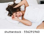 Stock photo portrait pretty young girl on bed in modern apartment in the morning she keeps eyes closed and 556291960