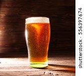 glass of beer on brown wooden... | Shutterstock . vector #556397674