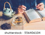 a man reading a book with cup... | Shutterstock . vector #556406104
