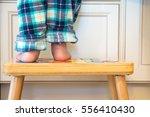 toddler boy's feet standing on... | Shutterstock . vector #556410430