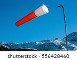 Small photo of Air sock or sleeve showing the direction and velocity of the wind blowing in the breeze on a snowy mountain slope in winter sunshine