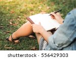 girl with pen writing on... | Shutterstock . vector #556429303