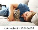 Stock photo child with kitten on grey sofa at home 556436554