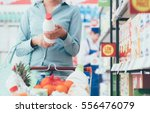 woman doing grocery shopping at ... | Shutterstock . vector #556476079