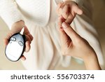 young girl testing blood sugar...   Shutterstock . vector #556703374