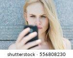 upset woman holding a cellphone. | Shutterstock . vector #556808230