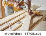 hammering nails into wooden... | Shutterstock . vector #557081608
